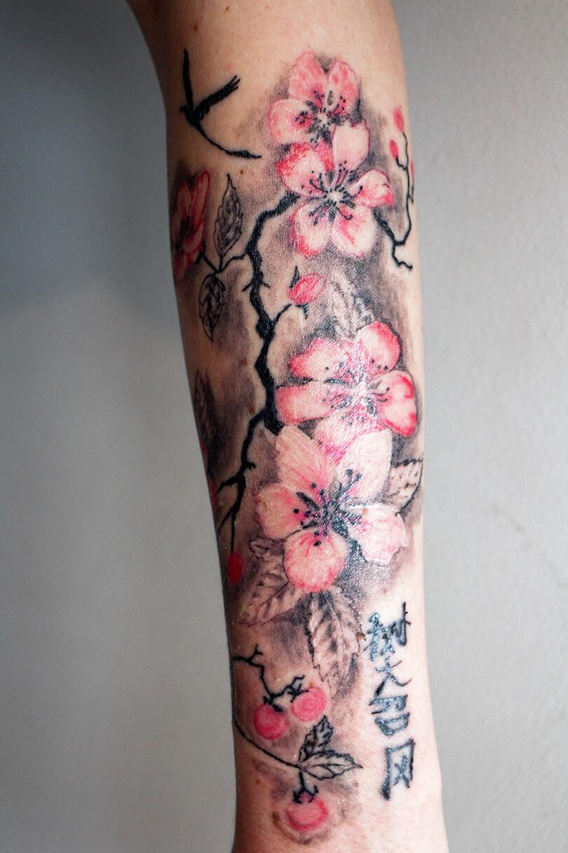 Cosmopolitan Tattoo Avant Bras Femme Fleurs De Cerisiers Couleurs Branchages Graphiques Motif Inspiration Japonaise