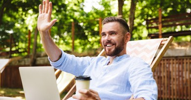Photo of smiling emotional young bearded man outdoors using laptop computer looking aside waving holding coffee.
