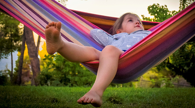 young girl in a colourful hammock