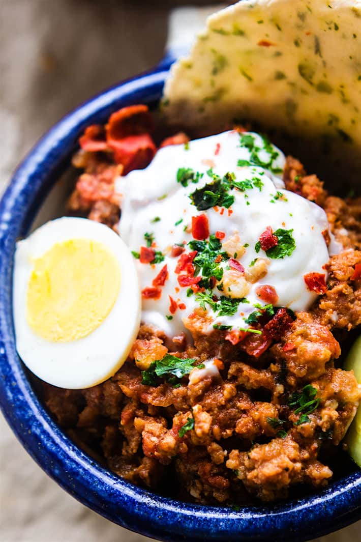 Grain Free Turkish Style Savory Breakfast Bowls. One pan is all you need to make these healthy savory breakfast bowls. Filled with spicy breakfast sausage, herbs, veggies, egg, and a tangy yogurt topping! Great for breakfast, brunch, or dinner.