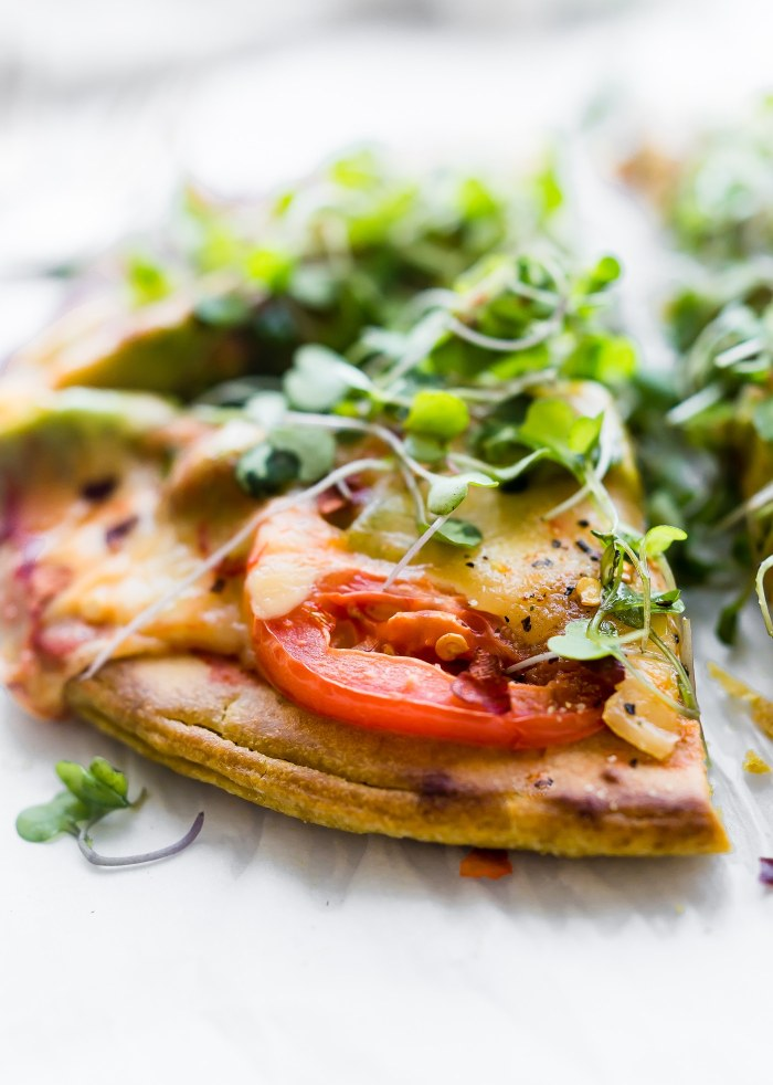 Avocado Tomato Gouda Socca Pizza recipe to love! Agrain free, gluten free Avocado Tomato Gouda Socca Pizza made withchickpea flour and topped with Avocado, Gouda, Tomato, and Sprouted Greens! Seriously easy to make, egg free, vegan option, OMG delicious!