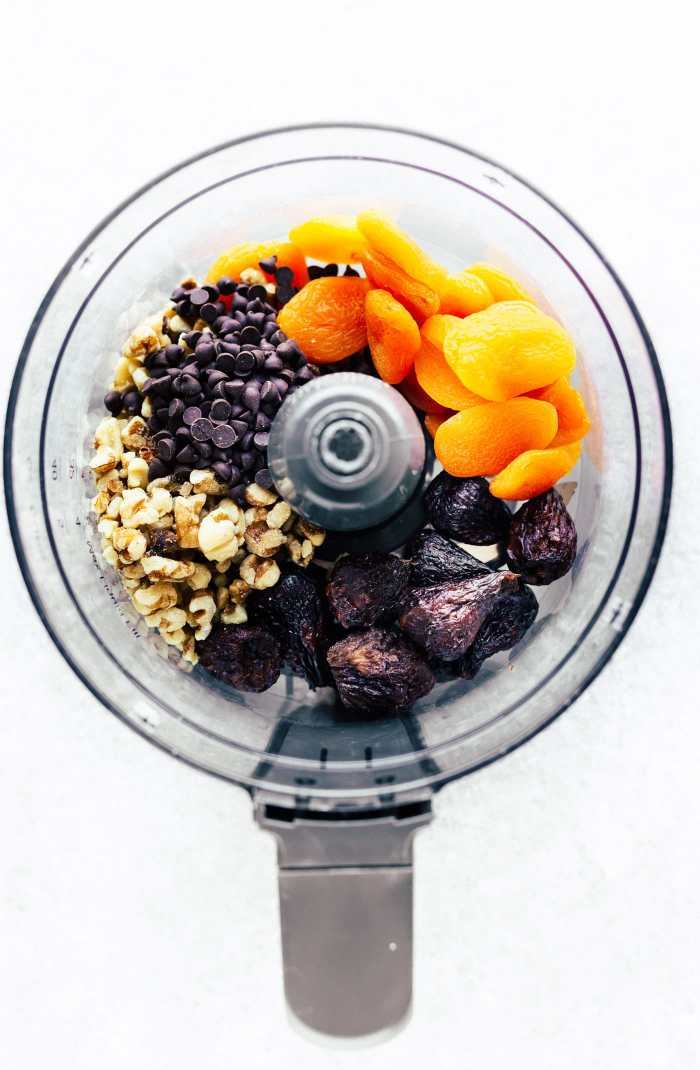 Ingredients in a food processor to make no bake Apricot Fig Bliss Bites