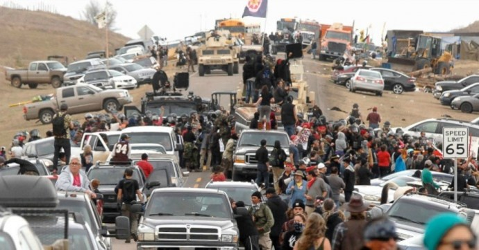 Photo of people, army vehicles, and many trucks and cars.