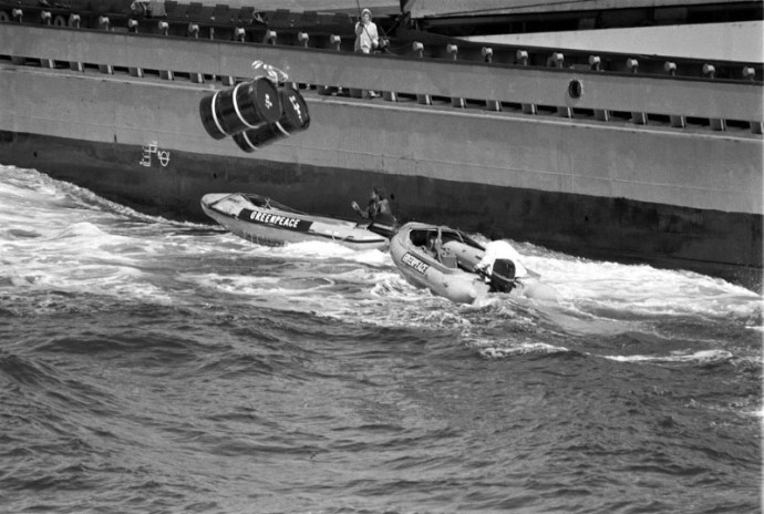 Greenpeace action protesting at the dumping of nuclear waste in the Atlantic by the dumpship RIJNBORG.  2 barrels being dropped on top of a Greenpeace inflatable causing it to capsize.    (Greenpeace Witness book page 34)  (The Greenpeace story book page 84)