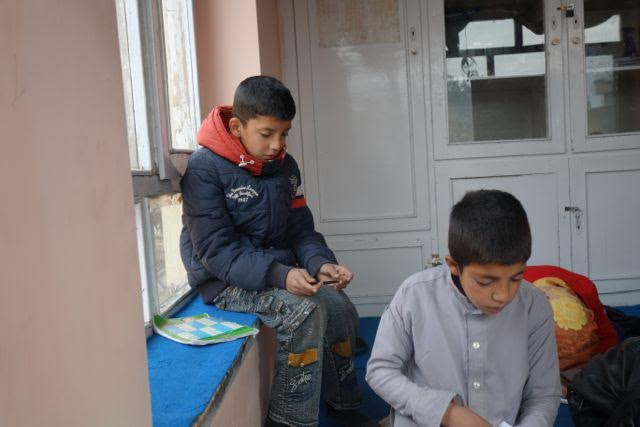 Shazad sits on a window school at the Borderfree Center where he studies at the Street Kids School