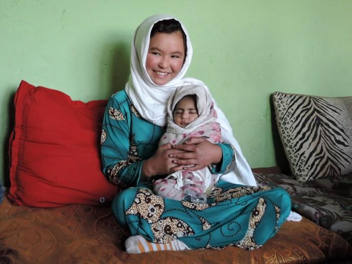 Jamila, age 11, holds a neighbor's newborn. Photo credit: Henrietta Cullinan