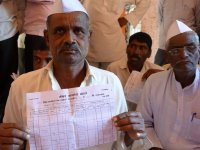A farmer in Nagur holds up an extract of his loan account from the credit cooperative society; further interest of 2-4 per cent gets added at the level of the societies