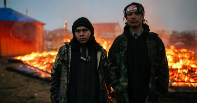 Chanse Zavalla, 22, left, and O'Shea Spencer, 20, right, stand in front of the remains of a hogan structure, set on fire ahead of the U.S. Army Corp of Engineer's deadline to leave the Oceti Sakowin protest camp on February 22, 2017 in Cannon Ball, North Dakota. (Photo: Stephen Yang/Getty Images)