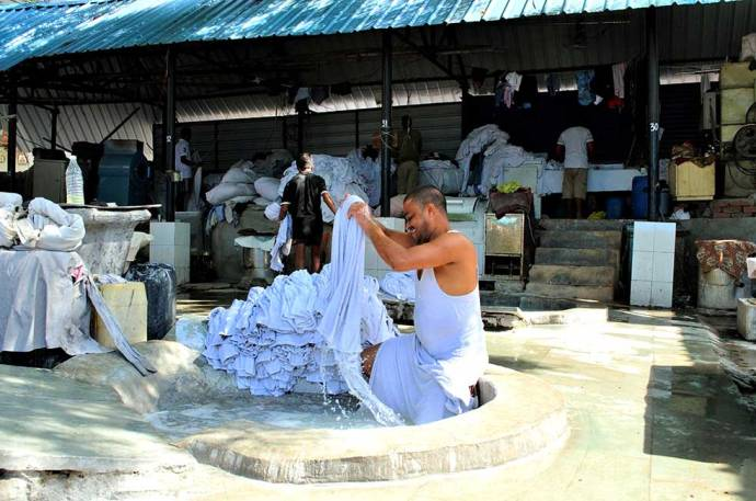 A washerman washing clothes inside the cement tubs at the ghat.