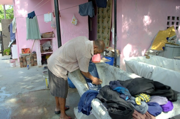 A washerman scrubbing clothes with detergent before washing them.