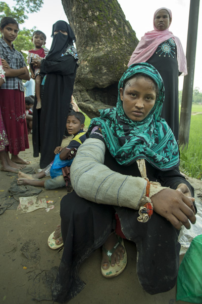 Rohingya Refugee at Balukhali near Bangladesh-Myanmar border, Cox's Bazar, Bangladesh. Husband was killed by Myanmar military. She was beaten by the Burmese mob and drove her out towards Bangladesh border. She has pain in the body yet could not but waiting for relief by the road.