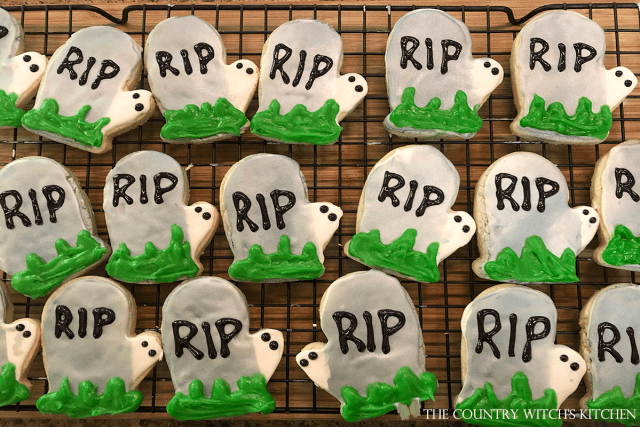 adding the grass decoration to the iced tombstone sugar cookies