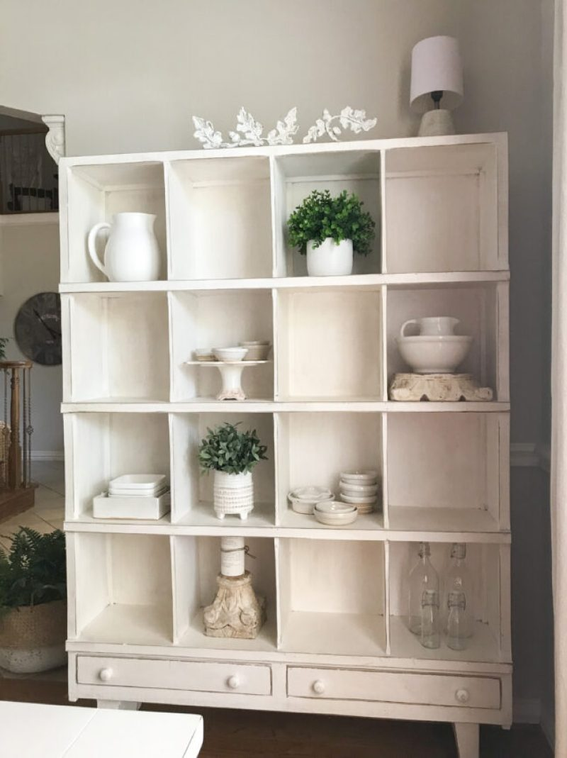 full cubby shelf with pottery and faux plants