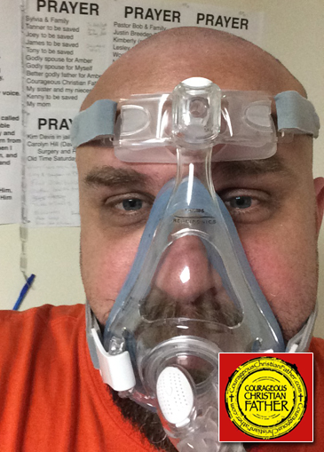 Steve wearing a CPAP mask and ready to go to sleep. You can also see his prayer wall in the background.