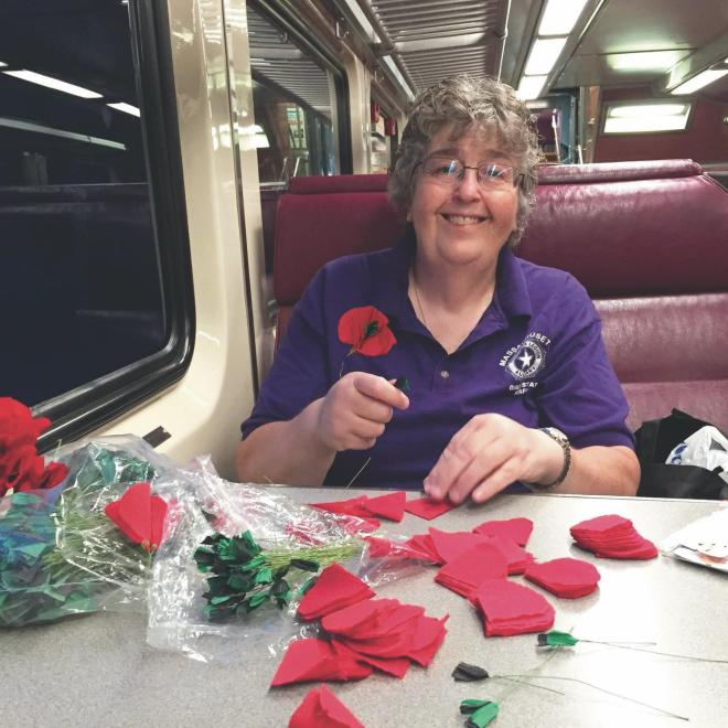 Wearing a poppy supports veterans | Pictured is Ann Fournier making the poppy flowers on the train.