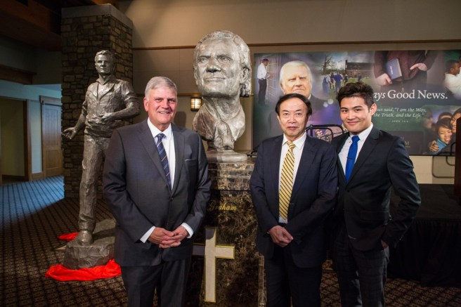 """Left to right: Franklin Graham, Chinese artist Yuan Xikun and the artist's son, Henri Yuan Xikun, posed for a photo with the bust entitled, """"Billy Graham as Messenger,"""" one of two sculptures unveiled. The second is in the background to the left."""
