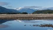 Bivouac aux bords d'un bras d'eau calme de la Skeena, entouré des sommets enneigés de la chaîne cotière