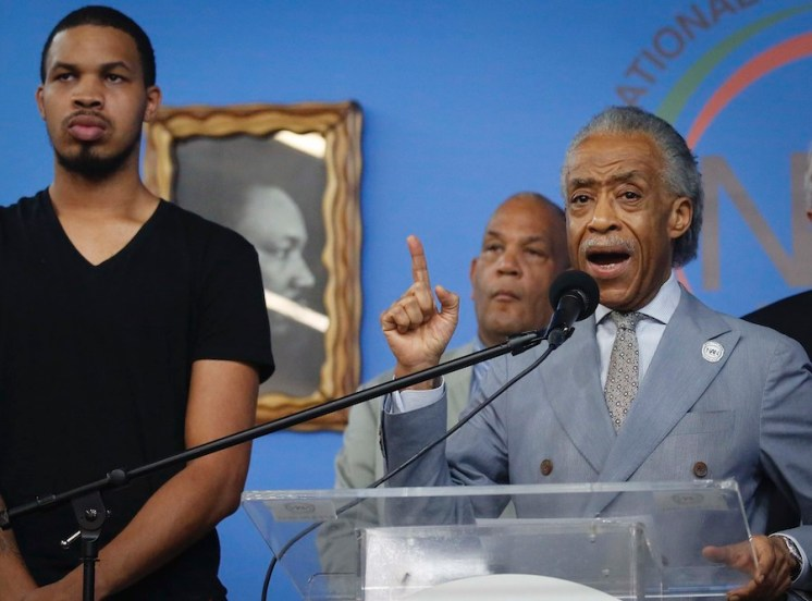 Eric Garner Jr., left, the son of chokehold victim Eric Garner, listens as Rev. Al Sharpton, right, founder of the National Action Network, speaks during a press conference after NYPD Commissioner James O'Neill announced his decision Monday to fire NYPD officer Daniel Pantaleo for the 2014 chokehold death of Eric Garner, at NAN headquarters in New York. (AP Photo/Bebeto Matthews)