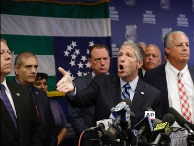 Patrolman's Benevolent Association President Patrick Lynch gestures during a Monday news conference at PBA headquarters in New York, following a decision to terminate NYPD Officer Daniel Pantaleo, who killed Eric Garner five years ago with a chokehold banned by department rules. Pantaleo's attorney Stuart London is at right. (AP Photo/Kathy Willens)