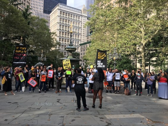 Activists with the group No New Jails rally in the park on Sept. 5 across from City Hall ahead of a land-use hearing on a proposal to close Rikers and replace it with four new borough jails. (Photo by AMANDA OTTAWAY/Courthouse News Service)