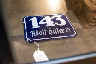 A street sign for '143 Adolf Hitler Place' is displayed for an auction at the 'Hermann Historica' auction house in Grasbrunn near Munich, Germany, on Nov. 20, 2019. A Geneva businessman says he has purchased Adolf Hitler's top hat and other Nazi memorabilia to keep them out of the hands of neo-Nazis and will donate them to a Jewish group. (Matthias Balk/dpa via AP)