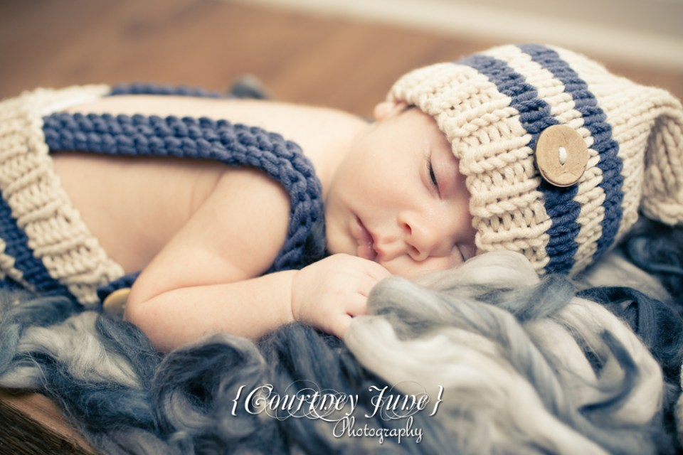 newborn photographer photographing a newborn in a knit jumper laying on stomach with one eye open