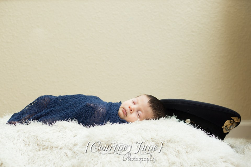 newborn photographer photographing a newborn swaddled in a navy blanket on a furry rug with a police officer's hat