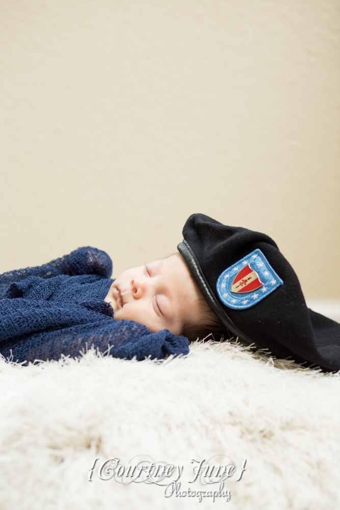 newborn photographer photographing a newborn portrait with daddy's army cap on
