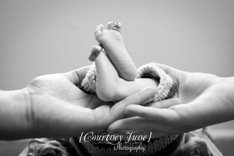 newborn photographer photographing an ewborn baby's feet with mom and dad's wedding rings