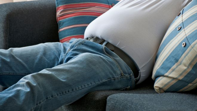 couch potato, bad posture, too much sitting, dangers of sitting, sedentary lifestyle, hamstring dominance, big gutt, obesity, man sitting on couch