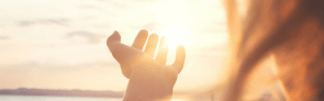 woman grasping at sun over water