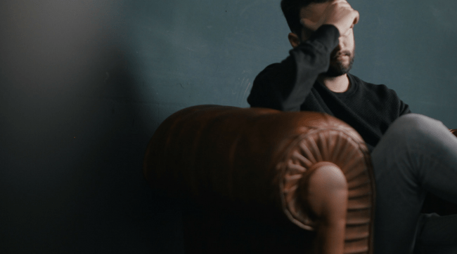 man sitting on leather couch