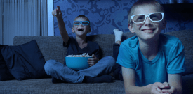 two boys watching movie at home