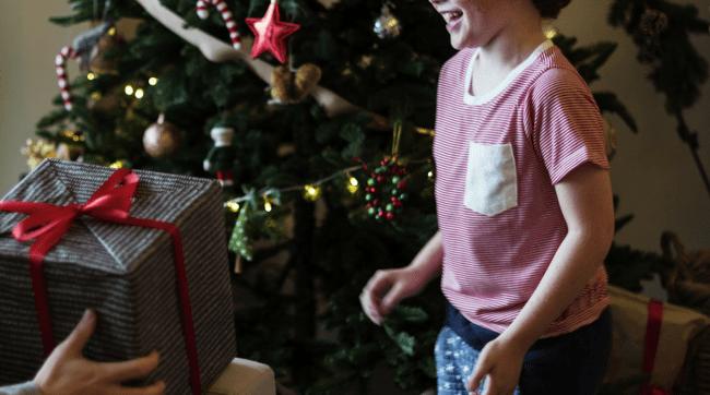 parent handing kid a Christmas present