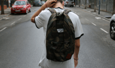 teenage boy walking down street with backpack