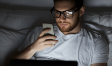 man looking at cell phone in dark bedroom