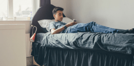 teen boy sitting on bed with smartphone