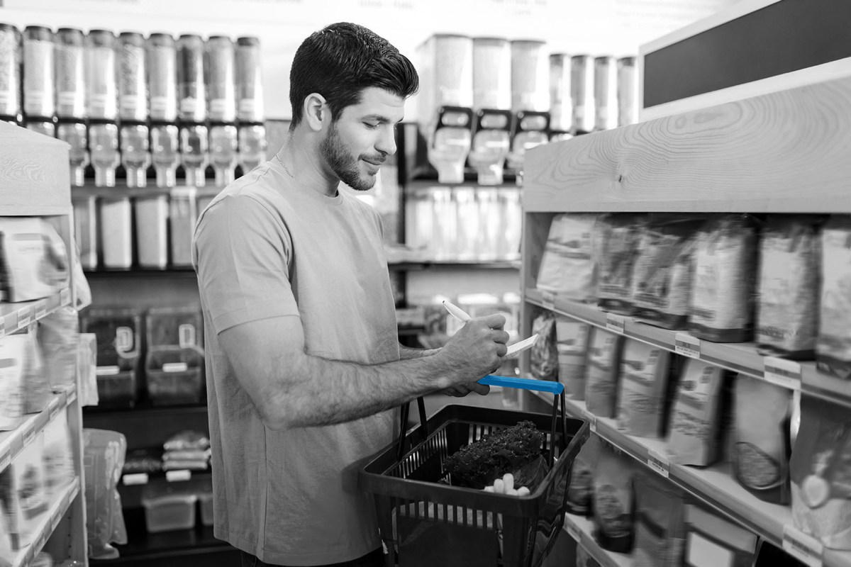 Smiling young man checking shopping list in supermarket