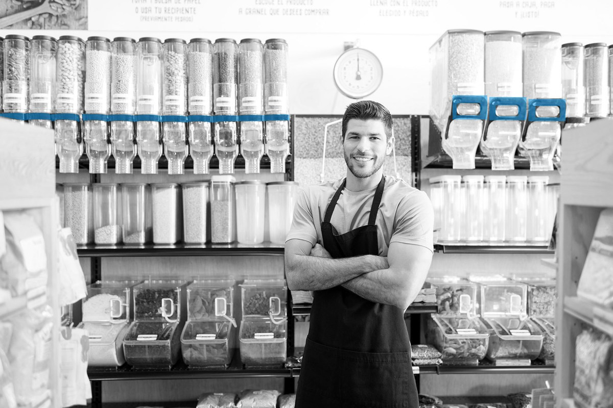 Confident Hispanic male owner standing with arms crossed in bulk food aisle at supermarket