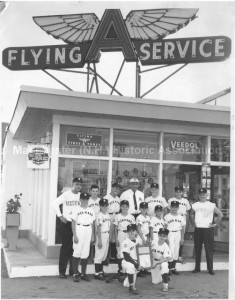 """Group photograph of Hickman's Little League team at Hickman's Service Station, with """"Flying A Service"""" sign at 16 Milford Street, Manchester. Photo identified as """"1961 South West Little League Champions - Wolf's Little League Park."""" 1st Row (holding plaque): Short Stop Bob Michaud, Secord Baseman Mike McDonald. 2nd Row: Outfielder Jim Alger, Outfielder Norm Bellemore, Infielder Bob Eldridge, Pitcher Bob Christo, Infielder Don Huot, Catacher Bill Prive; 3rd Row: Coach Don Anderson, Centerfielder Tom Caldwell, Pitcher Ron Boulanger, Sponsor Hap Hickman, Utility Man Jean Biron, Rightfielder Jim Norton, Manager Ed """"Casey"""" Forbush. Absent when photo was takere were Thirdbaseman Tim Mullen and Left Fielder Scott Keller. (Eric M. Sanford photographer). From the Manchester Historic Association Collection, used with their permission."""