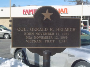 Photograph of Gerald J. Helmich recognition plaque, located in Manchester NH at the corners of -- and  -- Streets. Copyright of Martin Miccio for the City of Manchester, and used here with permission.