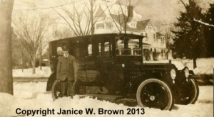 Charles A. Manning, chaffeur, in front of Mrs. Robert L. Manning's LaSalle.  On Elm Street, Manchester NH.