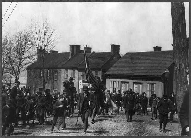 Members of Coxey's Army: men and boys, with flag bearer in center