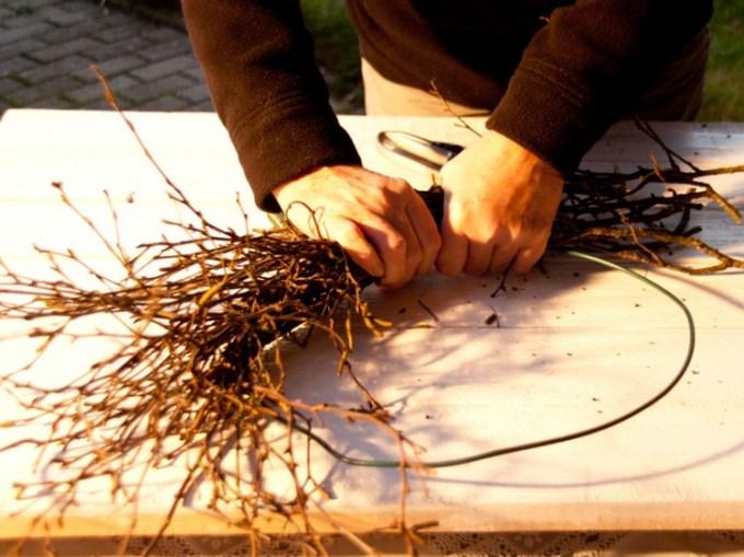 Die Zweige immer mit den Händen fest andrücken, so dass der Kranz rundherum gleichmässig wird.
