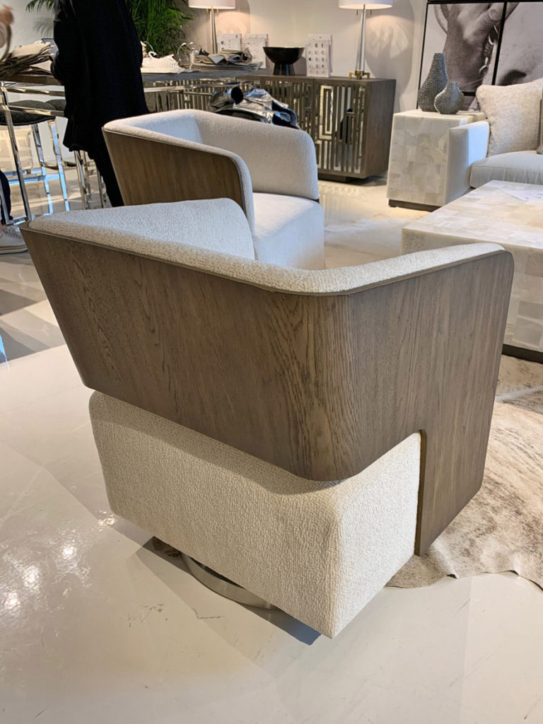Off-white swivel chair with wood grain frame at Highpoint Market