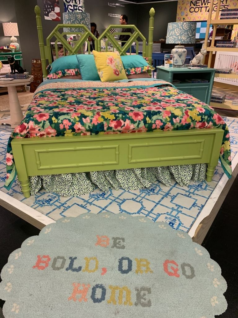 Green wood upholstered bed with floral pillows and comforter at Highpoint Market