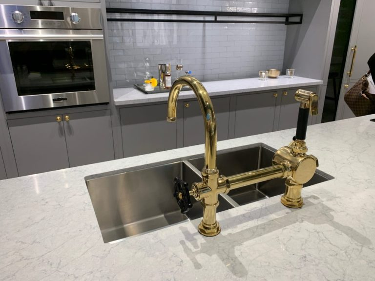Modern kitchen with grey cabinetry and white countertops with brass plumbing fixtures - Signature Kitchen Suite, Napa CA