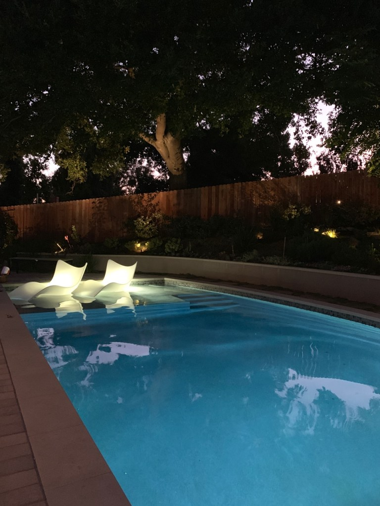 Sierra Madre, CA pool with illuminated chaise lounges sitting on a baja shelf.
