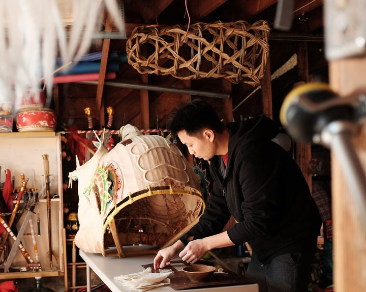 Travis Lum delicately repairs a lion head. Mark Markley photograph, CELEBRATION episode, Craft in America