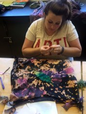 Nicole Roche prepares to appliqué a leaf onto her psychedelic shirt
